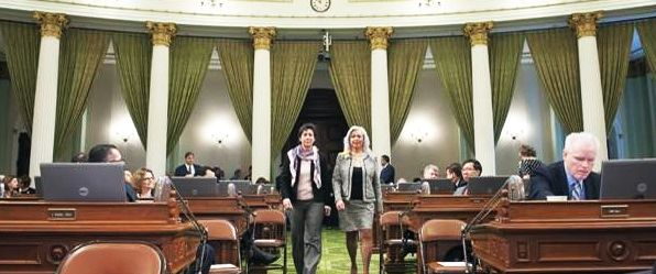 Assembly woman Susan Eggman, D-Stockton, left, accompanies Bonnie Lew down the aisle on the floor of the State Legislature in Sacramento.